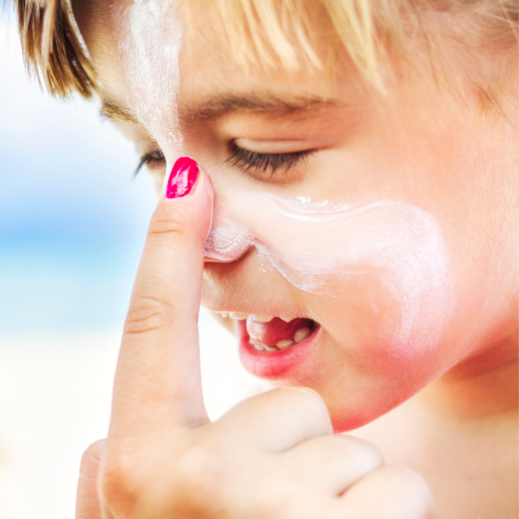 parent hand putting sunscreen on male child face