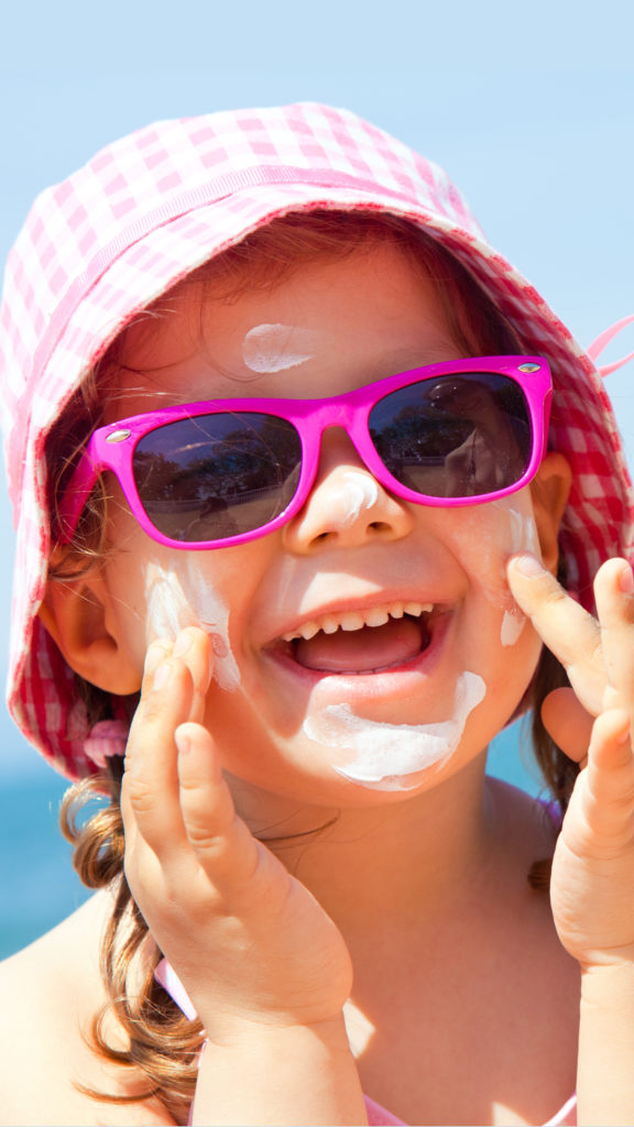 A toddler wearing a hat and sunglasses applying sunscreen to her cheeks.