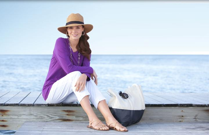 A woman sitting by the ocean wearing a sun hat and long layers for sun protection