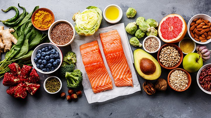 A flatlay of foods: salmon, berries, grapefruit, avocado, and more.
