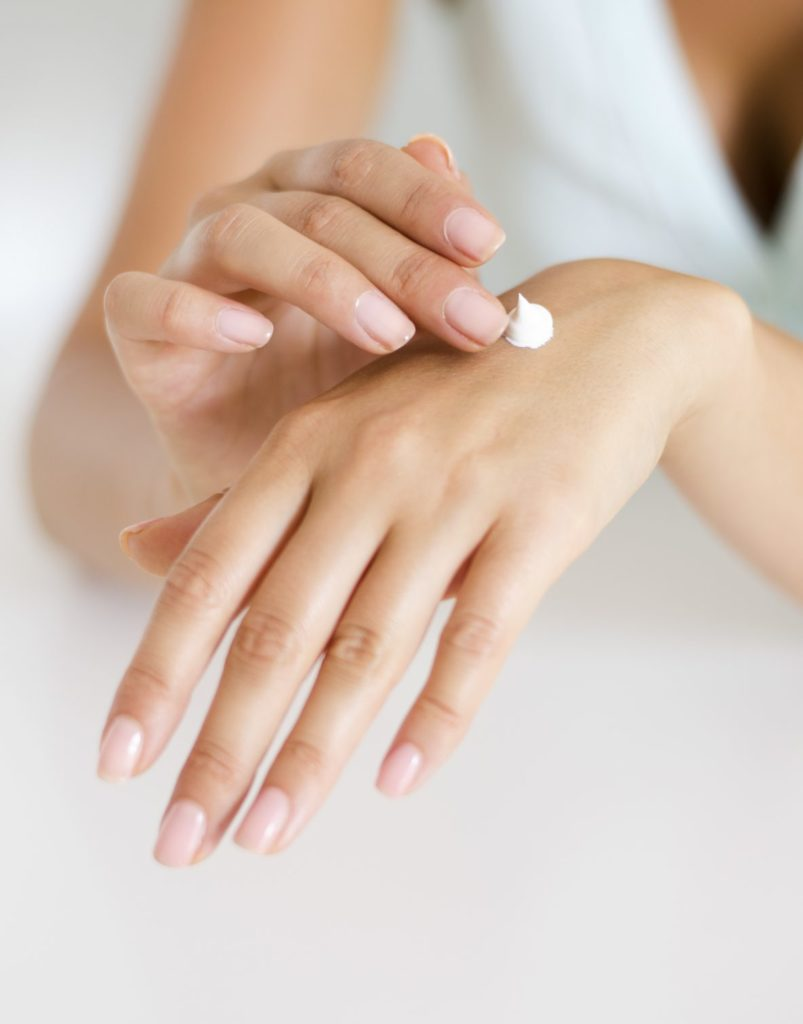 A photo of hands with a dollop of lotion on the back of one hand