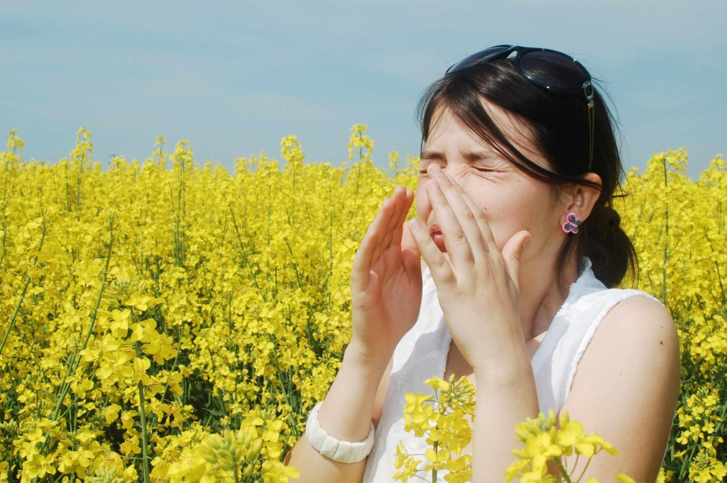 A woman sneezing in a field of wildflowers