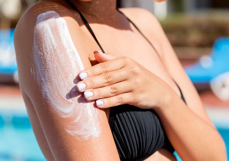 female in bathing suit putting sunscreen on shoulder